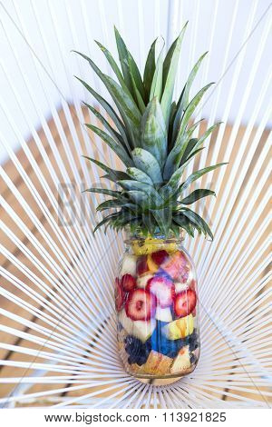 Healthy concept, mason jar filled with tropical fruits looking like a pineapple