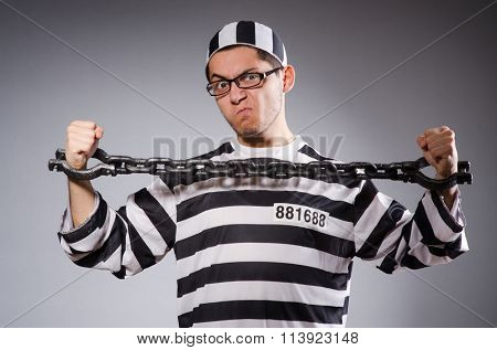 Funny prisoner in chains isolated on gray