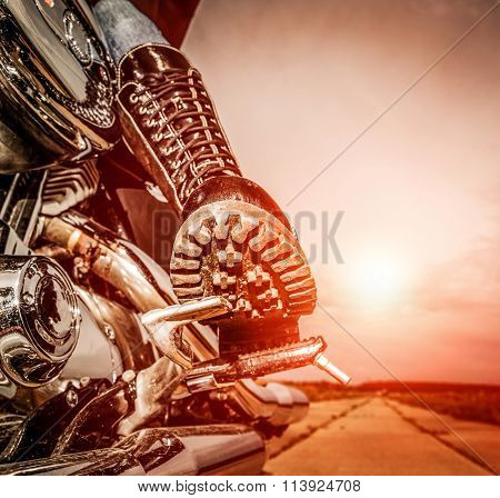 Biker girl riding on a motorcycle. Bottom view of the legs in leather boots.