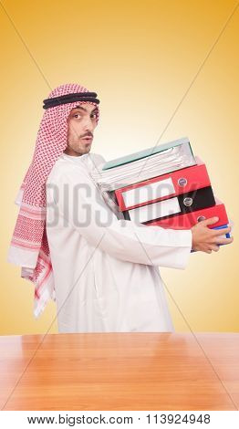 Arab businessman with many folders against gradient