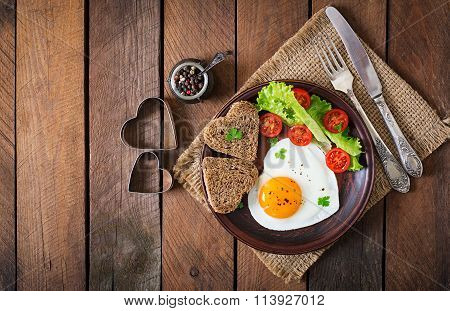 Breakfast On Valentine's Day - Fried Eggs And Bread In The Shape Of A Heart And Fresh Vegetables. To
