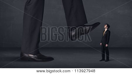 Giant person stepping on a little businessman concept on background