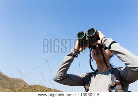 Asian Woman looking though the binocular