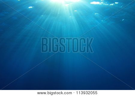 Underwater blue ocean background photo with sun and sunbeams