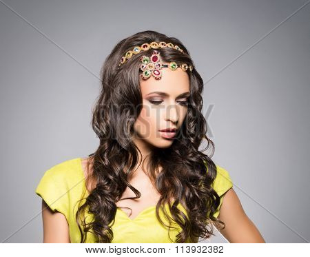 Gorgeous, sensual brunette wearing golden luxury coronet over grey background.