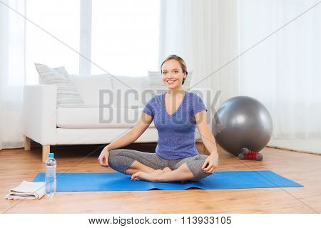 woman making yoga in lotus pose on mat