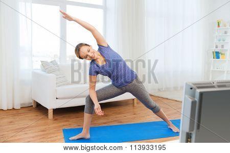 woman making yoga bikram triangle pose on mat