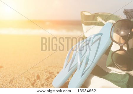Summer concept of bag and flip flops on a tropical beach.