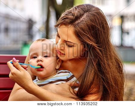 Portrait of happy beautiful mother feed her baby summer outdoors in park.