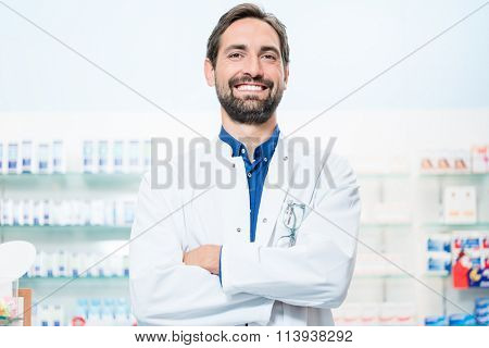 Apothecary in pharmacy standing at shelf with drugs
