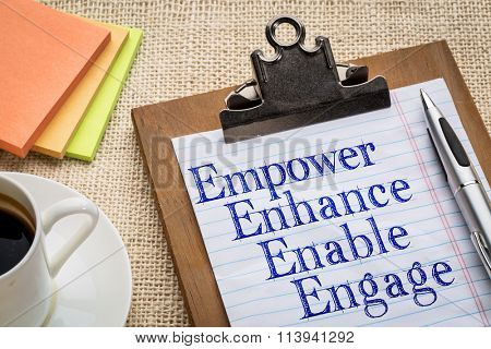 motivational leadership, coaching or business concept - empower, enhance, enable and engage  words on a clipboard with a cup of coffee