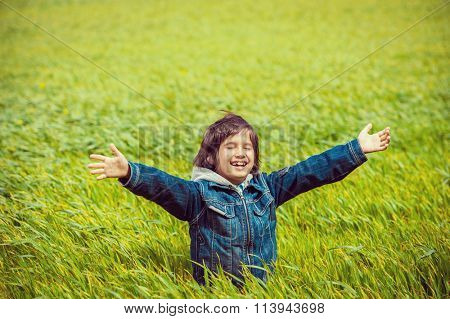 Excited kid on beautiful green yellow grass field