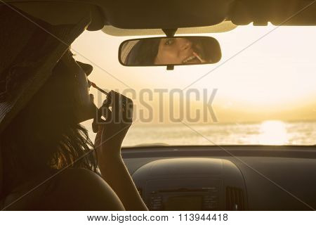 Woman applying lipstick and using rearview mirror in car at the sunset
