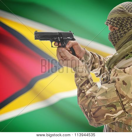Male In With Gun In Hand And National Flag On Background - Guyana