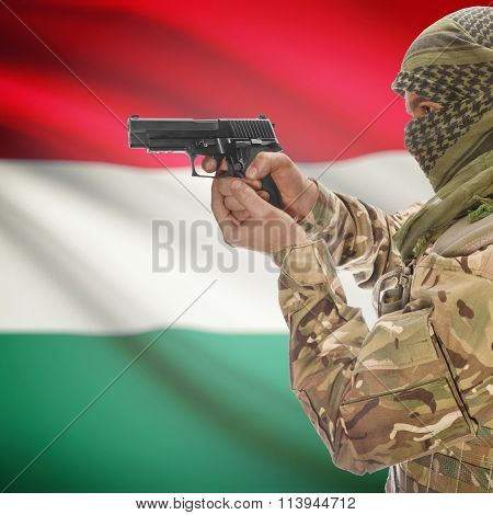 Male In With Gun In Hand And National Flag On Background - Hungary