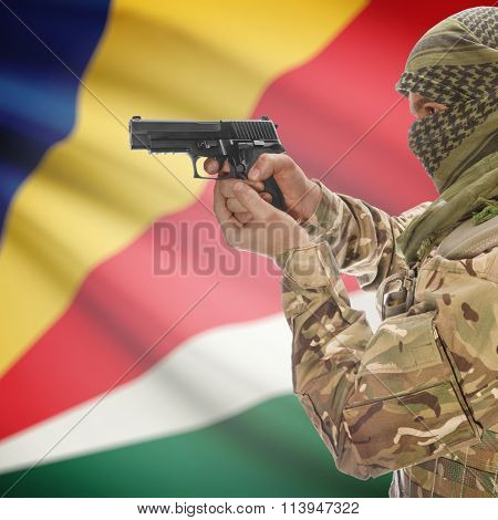Male In With Gun In Hand And National Flag On Background - Seychelles