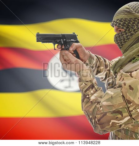 Male With Gun In Hand And National Flag On Background - Uganda