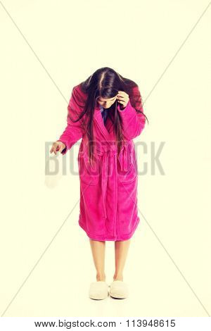 Woman in pink bathrobe with menstruation pad.