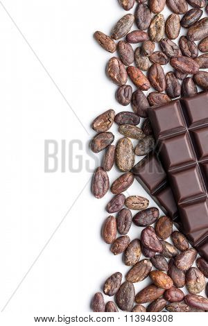 dark chocolate bars and cocoa beans on white background