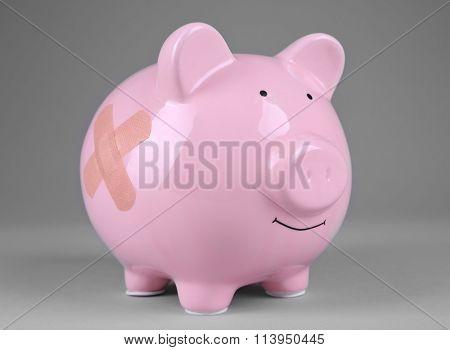 Piggy Bank with adhesive bandage on grey background