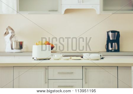 Wooden light table with toaster and dishes on a white kitchen background