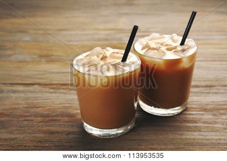 Two cups of ice coffee with straw on wooden background