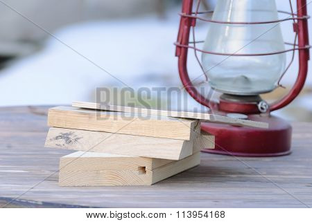 still life of wooden planks and oil lamp on a wooden table with a blurred background