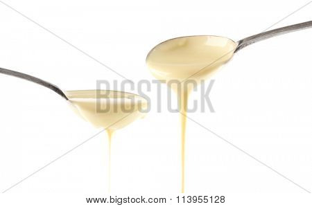 Condensed milk pouring from spoons, isolated on white