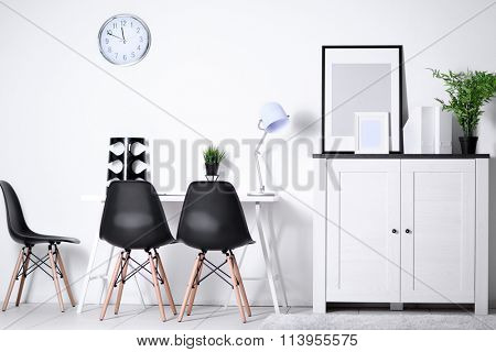 Room interior with commode, frames, chairs and table on white wall background
