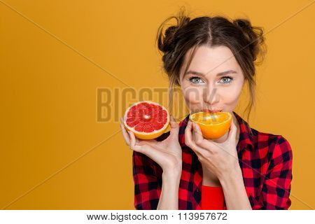 Lovely cute young woman in plaid shirt tasting orange and grapefruit over yellow background