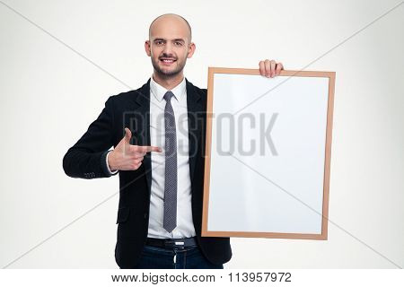 Happy confident business man in black suit holding blank board and pointing on it over white background