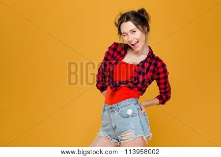 Playful happy young woman in plaid shirt and jeans shorts standing and winking over yellow background
