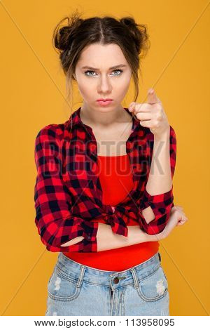 Annoyed unpleased young woman in checkered short standing and pointing on camera over yellow background