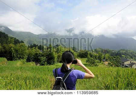 Chinese woman taking pictures of mountains