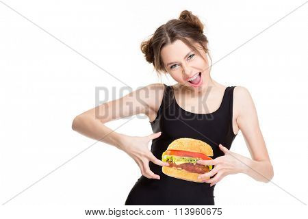 Playful shouting young woman in black top with hamburger print joking and touching her belly isolated over white background