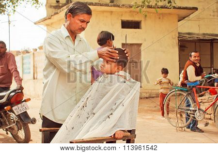 Unidentified Boy Sitting In Chair Of Rural Barber Shop And Doing New Hairstyle By A Barber