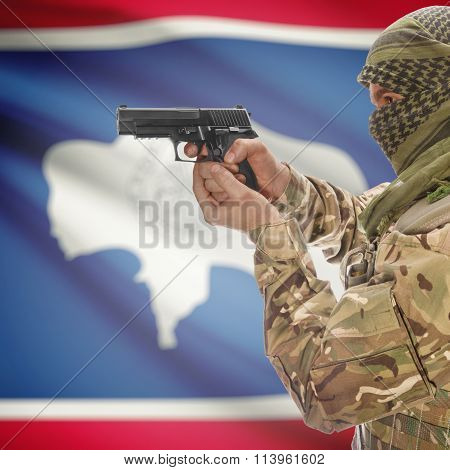 Male In With Gun In Hand And Flag On Background - Wyoming
