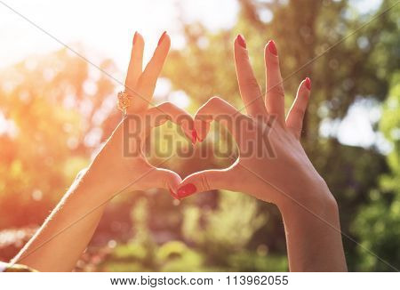 Woman's hand make a heart during beautiful spring sunset