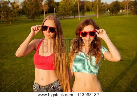 Two Young Slim Girls Holding Hands And Glasses In The Park