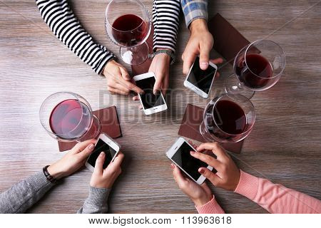 Four hands with smart phones holding glasses with red wine, on wooden table background