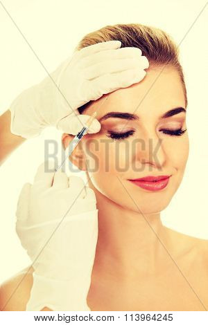 Young smiled woman is having facial botox injection.