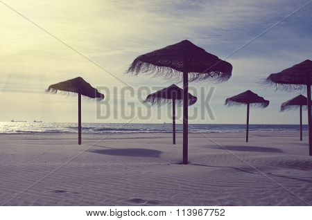 Wooden Sun Umbrellas Silhouettes On The Sea Beach. Vacation Concept In Vintage Color Tone. Costa Dor