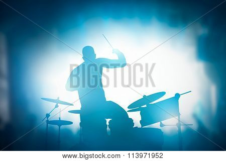 Drummer playing on drums on music concert. Club lights, artist show.