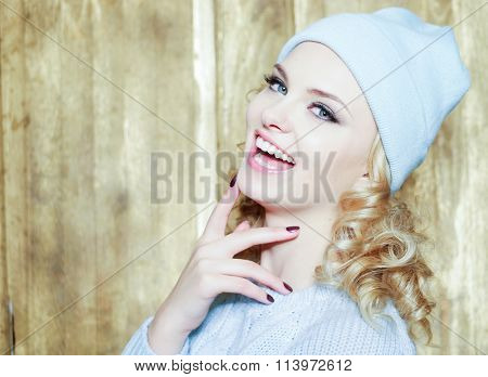 Gorgeous smiling young woman with blond ringlets and blue eyes laughing at the camera over a wooden background with copy space