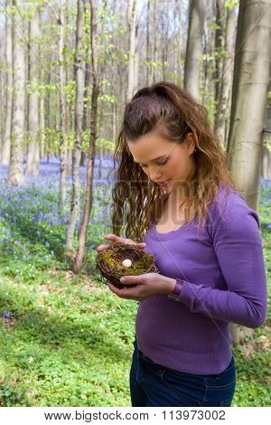 Pretty young woman holding a bird's nest in a bluebells springtime forest