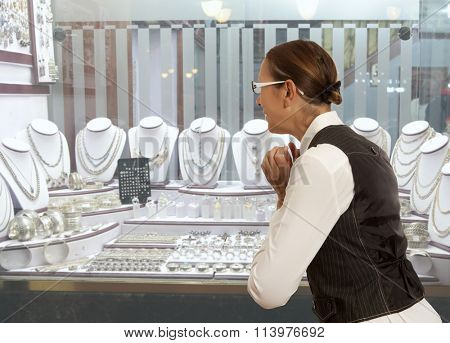 Woman looking to showcase or shop window. Shopping woman chooses jewelry in store
