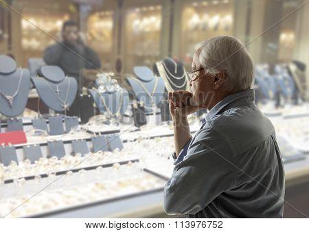 Senior man looking to jewellery showcase or shop window
