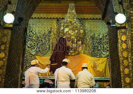 The senior monk wash Mahamuni Buddha image in ritual of the Buddha image face wash every morning.