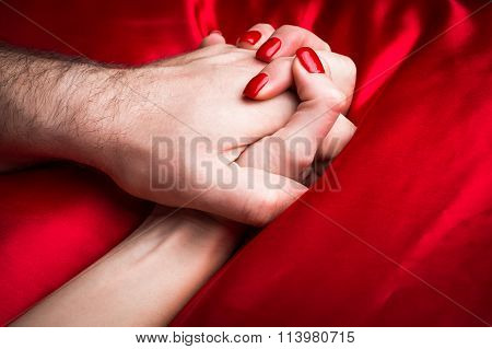 Young Couple Holding Hands Sensually On Red Silk Bed.