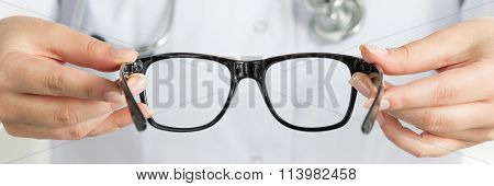 Female Doctor's Hand Holding Black Glasses